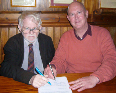 Peter Scott-Presland signs the contract while Griffith Vaughan Williams looks on